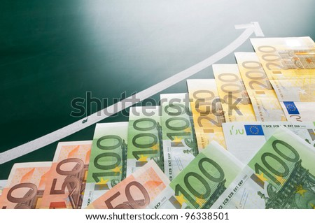 Euro banknotes and growing arrow on blackboard