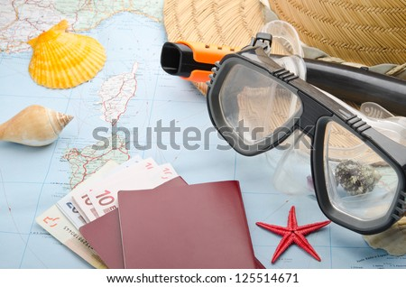 Euro banknotes and passport on a map with snorkel mask