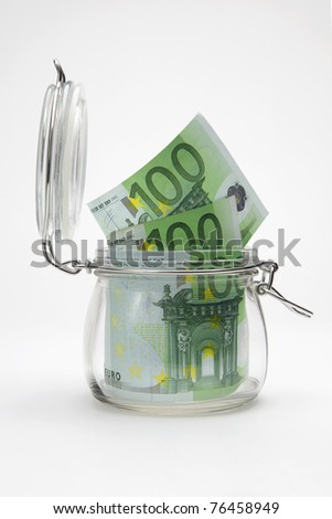 Euro banknotes in a glass jar on white background