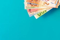 Euro banknotes isolated on blue background with soft shadows. Euro notes in corner on azure background with copy space. Euro cash of different values. Bunch of European money.