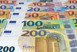 Euro banknotes of different denominations arranged in a row. Money, business and finances