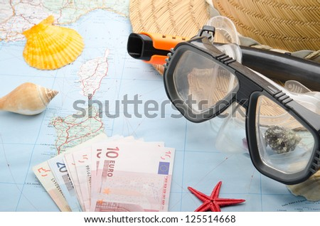 Euro banknotes on a map with snorkel mask
