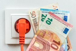 Euro banknotes with an electric plug - electricity cost concept