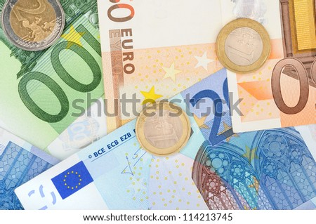 Euro bills and some coins in front of a white studio background