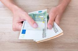 Euro cash in woman's hands.