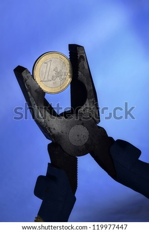 Euro coin and pliers symbolizing the European Union economic depression and the European currency under pressure