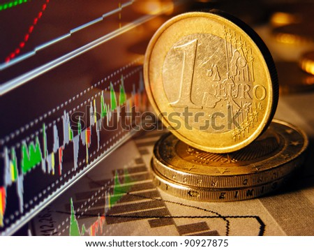 Euro coin and stock graph on a screen.