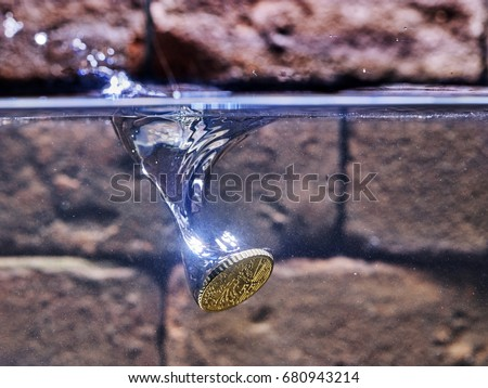 euro coin falling in a wishing well. #680943214