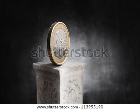 Euro coin on top of a plaster column.