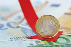 Euro coin with red decreasing arrow on euro banknotes - Concept of decrease in euro value and loss of money