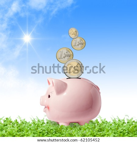 Euro coins falling into a pink piggy bank in a green field
