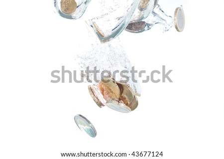 Euro coins falling into the clear water