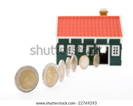 Euro coins in a row rolling into a house - closeup, isolated