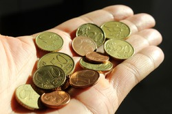 Euro coins in the hands of a boy who makes donations