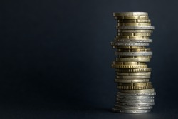 Euro coins of different denominations are messily stacked on a black blurred background with space for text