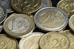 Euro coins of different denominations close-up lie sloppy on the plane