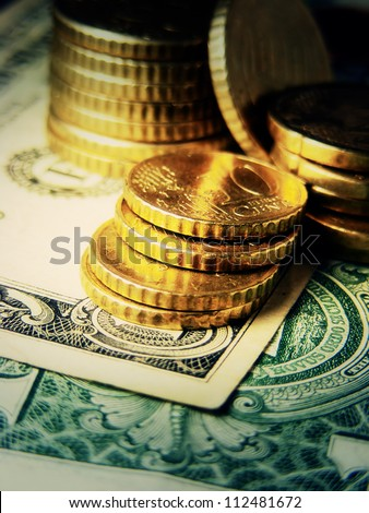 Euro coins on a dollar. Finance system concept.
