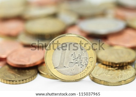 Euro coins. One Euro coin on the foreground. Shallow depth of field