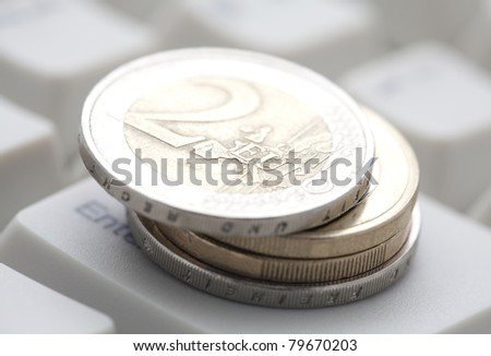 Euro coins over computer keyboard