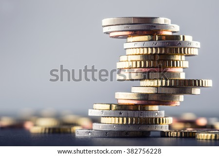 Photo of Euro coins stacked on each other in different positions.