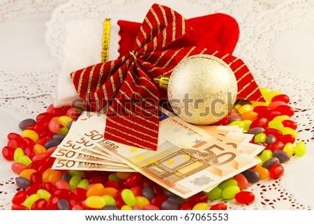Euro currency on jellybeans with Christmas bow, ornament, and small stocking depict a holiday bonus