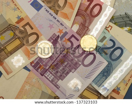 Euro (EUR) banknotes and coins money useful as a background or money concept - with a coin from Vatican (Pope Benedict XVI) and one from San Marino