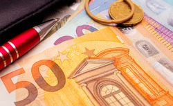 Euro ( EUR ) - European Union Currency. Euro banknotes on a table in close-up photo. A red pen, a rubber band and a 20 euro cent coin in the composition.