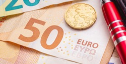 Euro ( EUR ) - European Union Currency. Euro banknotes on a table in close-up photo. A red pen and a 20 euro cent coin in the composition.