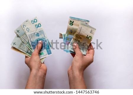 Euro money and Polski Zloty PLN in a womans hands on a white background. Euro in Poland. Euro vs Polski Zloty. Euro vs PLN #1447563746