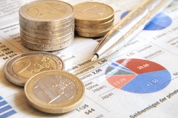 Euro money coins and ball pen on a global income report with charts