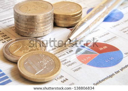 Euro money coins and ball pen on a global income report with charts - stock photo