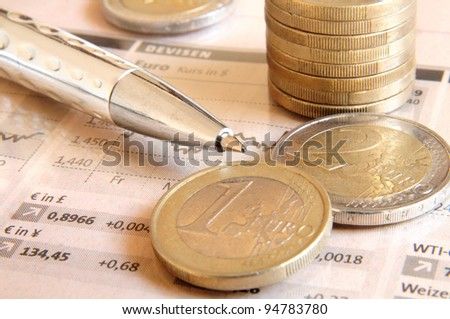 Euro money coins and silver colored ball pen on top of stock market chart
