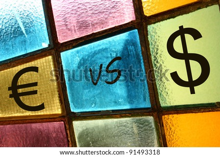 Euro versus dollar; euro and dollar signs painted on a stained-glass window