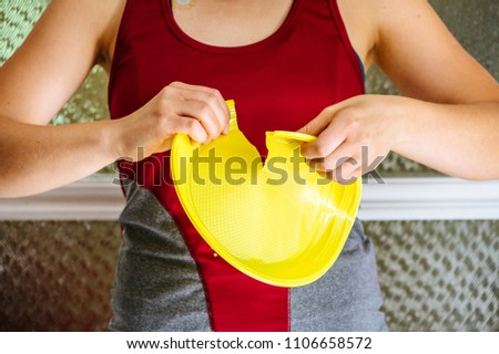 Europe ban on plastic dishes concept. Woman destroys yellow plastic plate.
