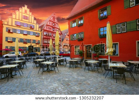 Europe, Bavaria, Dinkelsbuhl town, romantic road of Germany, chairs and tables for tourists on the square and colorful red-yellow buildings at evening, discover yourself touristic places