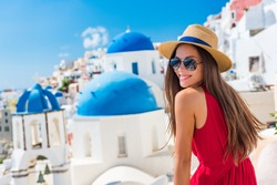 Europe Greece Santorini travel vacation woman on famous santorini Oia island travel destination. Happy young tourist girl in hat and sunglasses relaxing at blue dome church. Summer wanderlust.