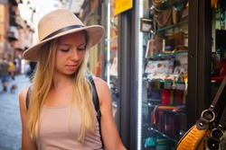 Europe Italy travel summer tourism holiday vacation background fashion - young attractive Caucasian smiling beautiful blonde girl student face making shopping on sale of hand bag near shop window