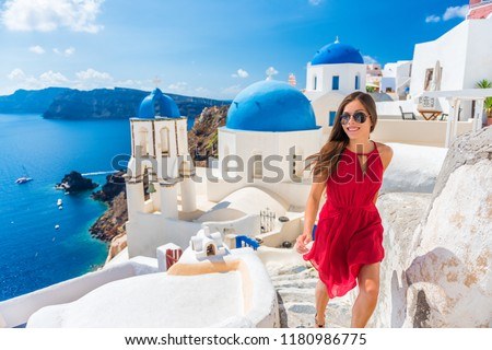 Europe summer vacation tourist woman walking in Oia city at three blue domes church, Santorini, Greece. famous cruise travel destination, Mediterranean Sea. #1180986775
