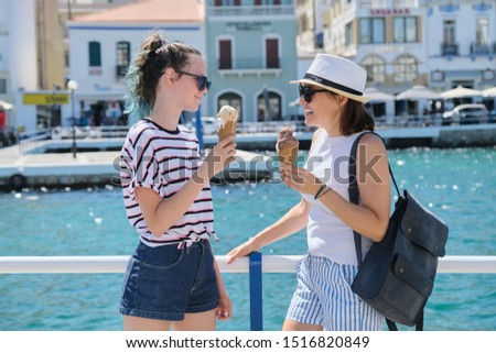 Europe tourist travel cruise vacation. Happy mother and daughter teenager with ice cream talking walking. Greece Mirabello Bay, Agios Nikolaos