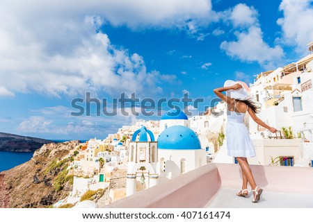 Europe tourist travel woman in Oia, Santorini, Greece. Happy young woman looking at famous blue dome church landmark destination. Beautiful girl in white dress on visiting the Greek island. #407161474
