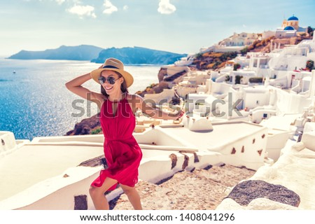 Europe travel fun - woman tourist running of joy in Santorini city luxury holiday destination. Cruise in Greece for summer holidays. Asian girl in red dress and hat with greek white houses background.