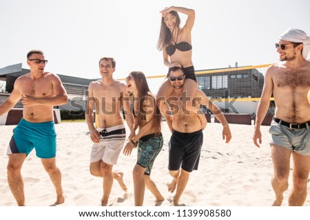 European adult people, cheerful guys and girl, spending their leisure time on hotel sandy volleyball field, having fun, living healthy active lifestyle, doing sport on beach.