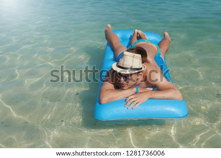 European boy and dad laying on blue floater on sea water surface. #1281736006