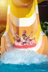 European boy and mom gliding down slide in waterpark. They enjoy the fun and holding hands wide open.