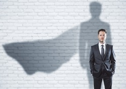 European businessman with super hero cape shadow standing on brick wall background. Leadership and success concept