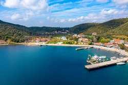 European country village on Mediterranean sea shore with coastline pier for fishing boats. Small resort town on green tree mountains summer background