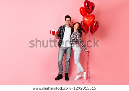 European couple posing in anniversary. Studio full length shot of man embracing wife and holding present.
