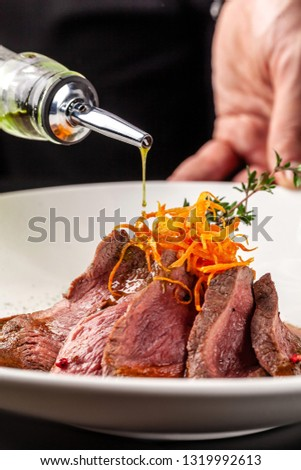 European cuisine. Marinated veal with roast Medium rare. Degree of roasting. Chef pours beef olive oil. Serving dishes in restaurant in a white plate. background image, copy space #1319992613