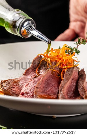 European cuisine. Marinated veal with roast Medium rare. Degree of roasting. Chef pours beef olive oil. Serving dishes in restaurant in a white plate. background image, copy space #1319992619