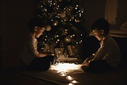 European family, two boys near the Christmas tree. Evening mood and authentic photography. Two brothers with a garland near the Christmas tree.